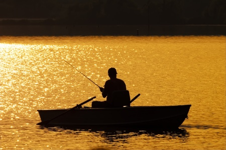 A man fishing from a small boat as the sun sets over a lake
