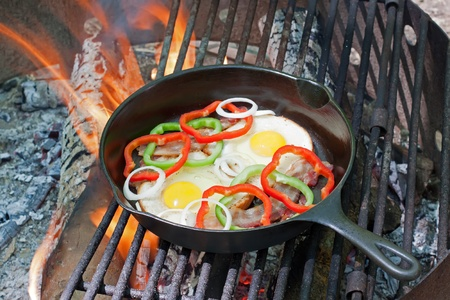 A breakfast of eggs,toast,bacon,onions and peppers