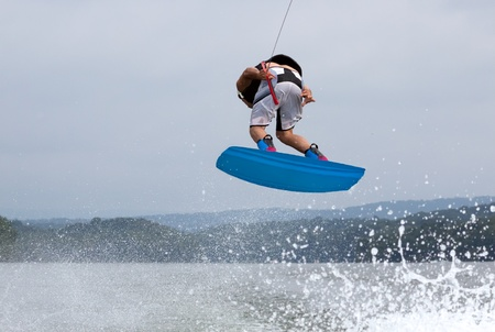 Wakeboarder doing 360 degree turn after jumping Stock Photo