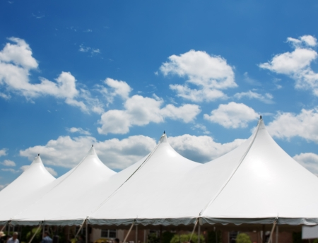 outdoor event: White event tent against a blue sky