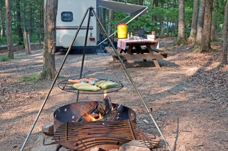 An outdoor grill at a Pennsylvania State Park with a picnic table and camping trailer in the background