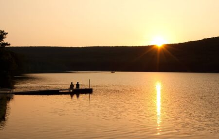 A couple sitting on a boat dock watching reflections on as the sun sinks over the mountain  Stock Photo - 14933262