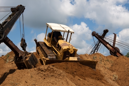 digger: An old bulldozer pushing soil off the top of a huge stockpile  Stock Photo