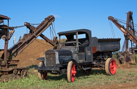 An old dump truck in a field with excavating equipment photo