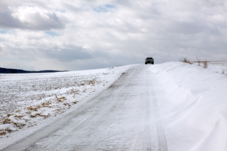 Snow blowing across a road in rural Pennsylvania  Stock Photo