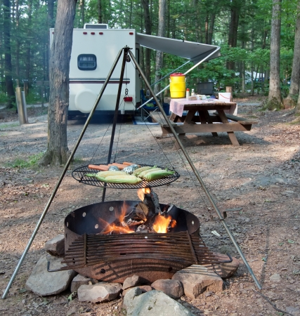 trailer: An outdoor grill at a Pennsylvania State Park with a picnic table and camping trailer in the background