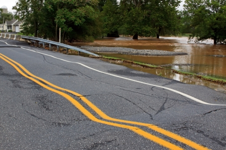 A rural road and bridge severely damaged by heavy flooding   Stock Photo