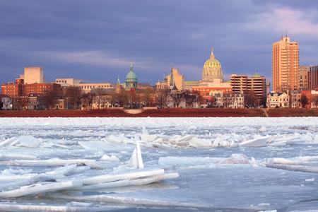winter thaw: Harrisburg, Pennsylvania,illuminated by evening sunlight as viewed from City Island across the frozen Susquehanna River