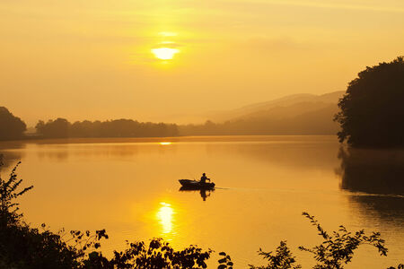 A lone fisherman moves out on a lake in a small boat as the sun breaks through dense morning fog