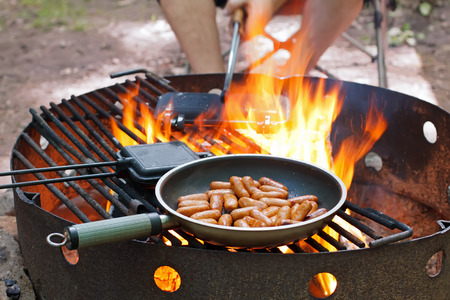 Frying small sausages over an open outdoor fire