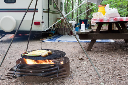 Corn and potatoes on an outdoor grill at a public park with a picnic table and camping trailer in the background  Stock Photo