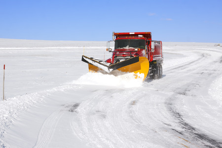 A snowplow truck removing snow from a winding rural road on bright winter day.