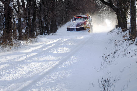 A snowplow truck removing snow from a tree lined rural road on a cold winter day. photo