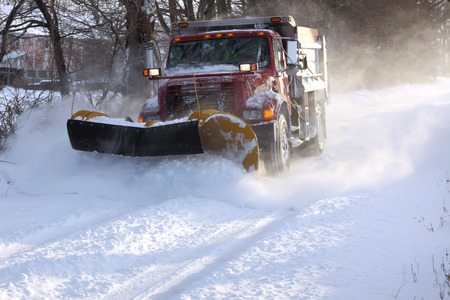 A snowplow truck removing snow from a tree lined rural road on a cold winter day.