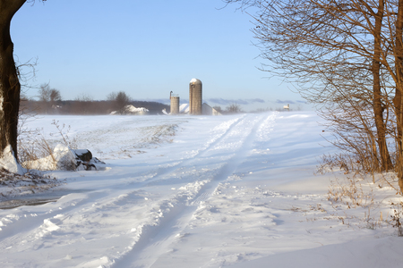 Snow blowing over a rural road in Lancaster County, Pennsylvania, USA.