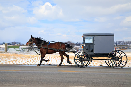 An Amish Carriage travels in snow covered rural Lancaster County, Pennsylvania, USA. 스톡 콘텐츠