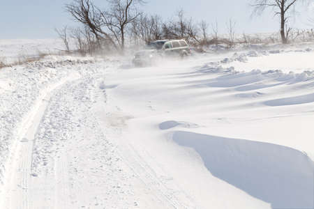 covered in snow: A vehicle driving in blowing drifting snow on a rural road in Pennsylvania, USA. Stock Photo