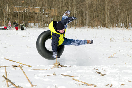 cropland: A young boy is thrown off his snow tube while tubing with friends on rural cropland.