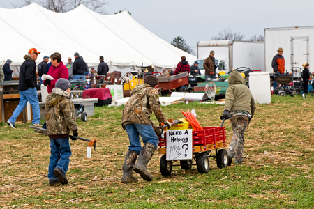 antiques: PENRYN, PENNSYLVANIA - MARCH 19, 2016: Young boys helping at annual  Mud Sale to benefit Penryn Fire Co.#1 and  Limerock Parochial School. Sale items include quilts, tools, food, crafts, farm equipment and antiques. Editorial