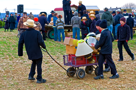 amish: PENRYN, PENNSYLVANIA - MARCH 19, 2016: Amish boys helping at annual  Mud Sale to benefit Penryn Fire and  Limerock Parochial School. Sale items include quilts, tools, food, crafts, farm equipment and antiques.