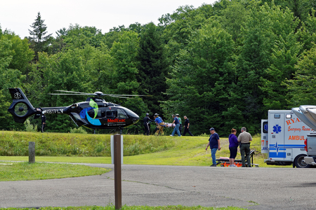 bystanders: BARNESVILLE, PA- JULY 3, 2016: A medical helicopter flies into Locust Lake State Park to transport a person needing emergency health care.