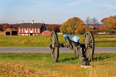A cannon and a barn on the battlefield at Gettysburg National Military Park, Adams County, Pennsylvania, USA. Stock Photo