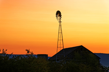 A beautiful sunrise on a rustic Amish barn with a windmill in Pennsylvania, USA.