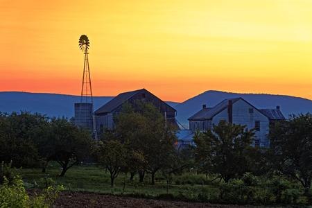 A beautiful sunrise on a rustic Amish farmstead with a windmill in Pennsylvania, USA.