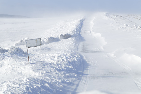 A rural mailbox by a country road which is closing with blowing drifting snow in Pennsylvania, USA.