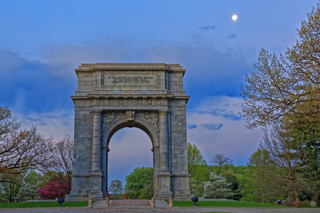 monument historical monument: Springtime dawn with the moon shining at Valley Forge National Historical Park in Pennsylvania, USA.The National Memorial Arch is a monument dedicated to George Washington and the United States Continental Army. Stock Photo