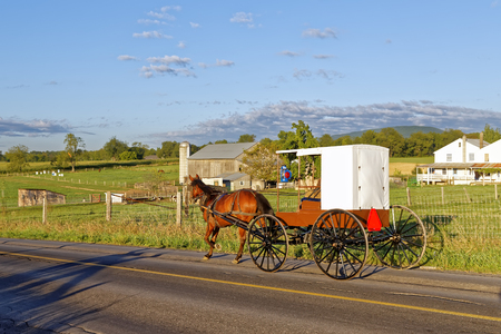 An Amish horse and carriage travels on a rural road in Mifflin County, Pennsylvania, USA.
