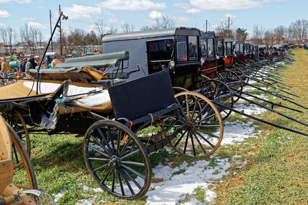 GORDONVILLE PENNSYLVANIA - March 11, 2017: Amish carriages for sale at annual spring auction `Amish Mud Sale` to benefit the Fire Company. Sale items include quilts, antiques, crafts, food, sporting goods, tools, farm equipment, and horses.