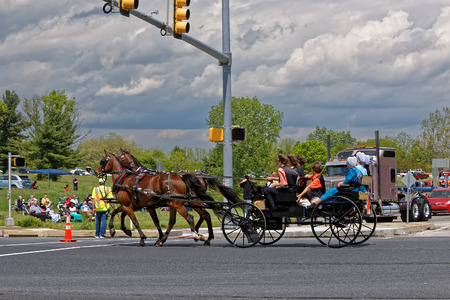 LANCASTER PA - MAY 14 2017: An Amish carriage passes the Make-A-Wish Foundation truck convoy. On the Mothers Day annual fundraiser truckers grant a Lancaster County wish ride to children with life-threatening illnesses.