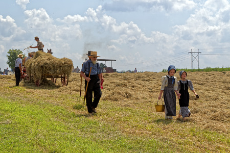 NEW HOLLAND, PENNSYLVANIA - August 4, 2017: Two young Mennonite girls with a pail and cup carry water for the hay crew at Big Spring Farm Days. This is an annual event demonstrating traditional threshing and harvesting methods, using restored antique and