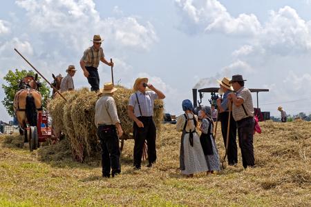 新しいオランダ、ペンシルバニア - 2017 年 8 月 4 日: メノナイトの 2 つの若い女の子は、ビッグ スプリング農場の日で干し草の乗組員に水を取る。伝 報道画像