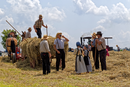 NEW HOLLAND, PENNSYLVANIA - August 4, 2017: Two young Mennonite girls take water to the hay crew at Big Spring Farm Days. This is an annual event demonstrating traditional threshing and harvesting methods, using restored antique and vintage tools. Redakční