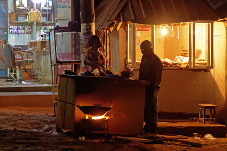 WAKISO UGANDA - SEPTEMBER 3, 2017: A street vendor prepares food after nightfall in Wakiso District located in the Central Region of Uganda, Africa.