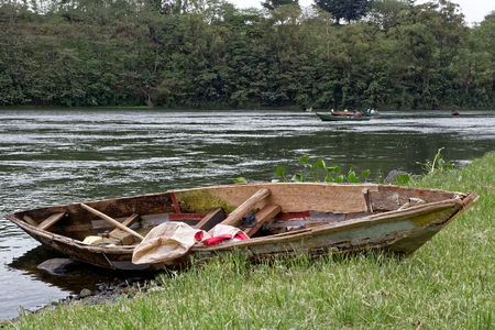 An old wooden rowboat on the Nile River in Uganda. Stock Photo