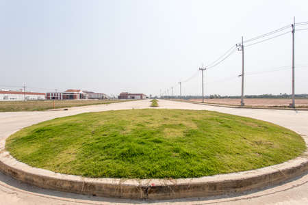 green grass circle and arrow with long road Banco de Imagens