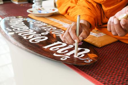 Monnik maakt gezegend teken op houten bord Stockfoto