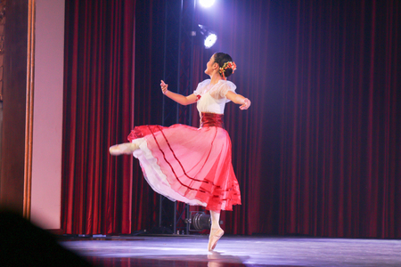 balletic: woman ballerina who wear romantic tutu costume is standing with right foot toe on stage