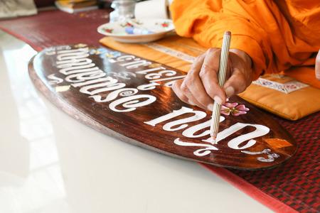 Monnik maakt gezegend teken op houten bord door zakpoeder en goud,