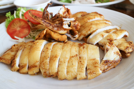 grilled squid on white dish with vegetables Banco de Imagens