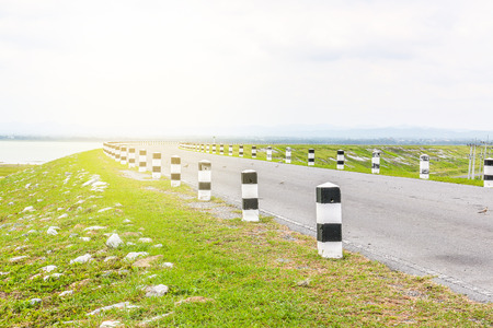 curve road: white and black pole barrier and curve road with dark sky and light effect