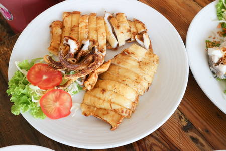 grilled squid on white dish and wood table Stock Photo