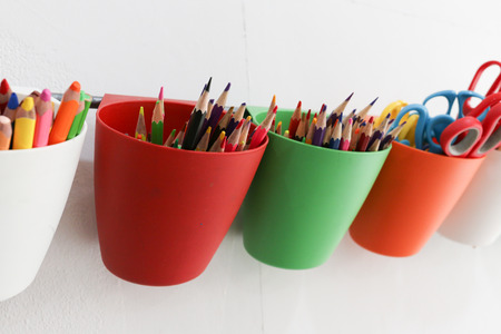 colorful pencils on red cup is hanged on the bar with white wall