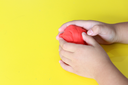 kid knead red play dough on yellow table