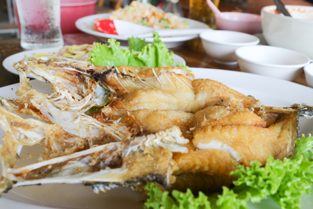deep fried snapper fish with fish sauce on white dish