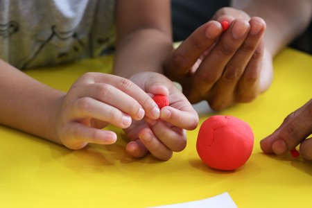 kid knead red play  on yellow table with parent