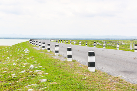 white and black pole barrier and curve road with dark sky Stock Photo